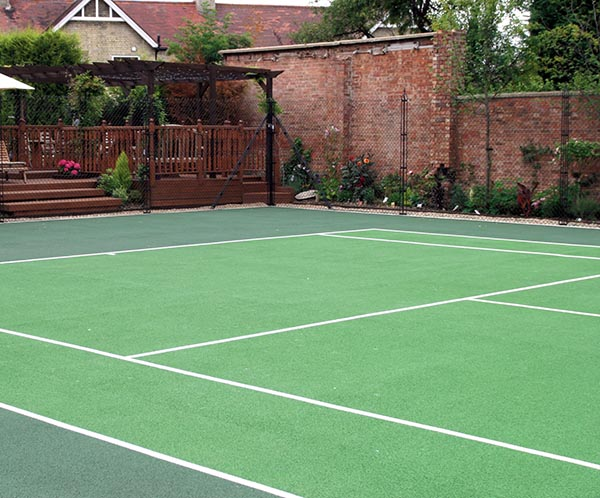 Garden court by Cotswold Tennis courts - synthetic sports surfaces (sometimes known as fake grass) offer a syuperb playing experience.