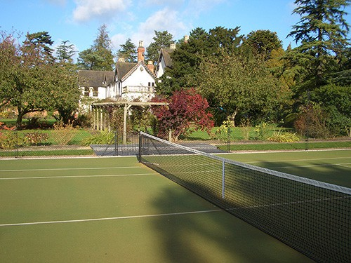 En Tout Cas tennis court with a synthetic grass surface (often called Astroturf or Fake Grass).