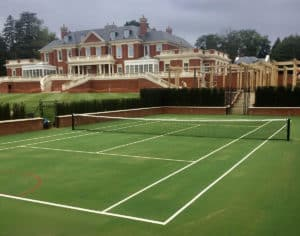 En Tout Cas tennis court fencing.. Obelisk fencing and a retaining wall form the frame to a just-laid Savanna court. Built by En Tout Cas