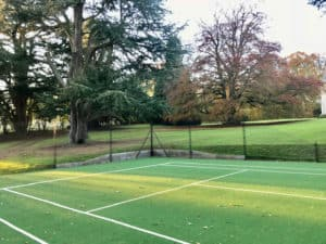 Savanna with an obelisk fence and small retaining wall. En Tout Cas tennis court fencing.
